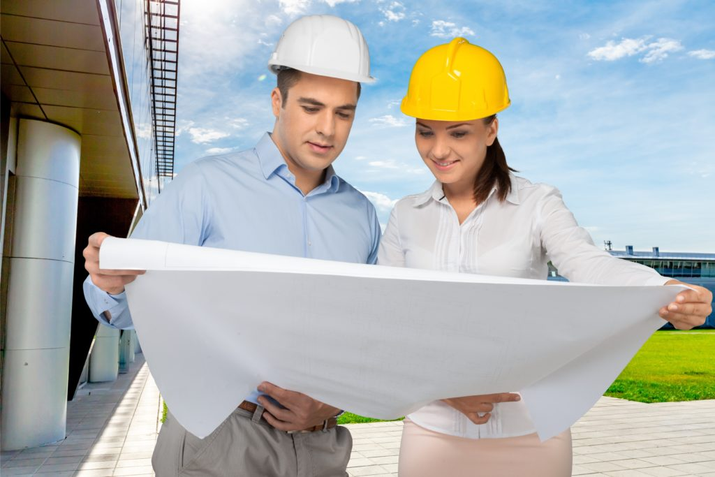 man and woman outside in hard hats looking at construction plans