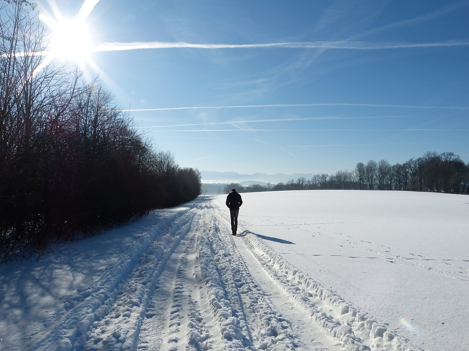 person walking in the snow with sun shining wearing sunscreen